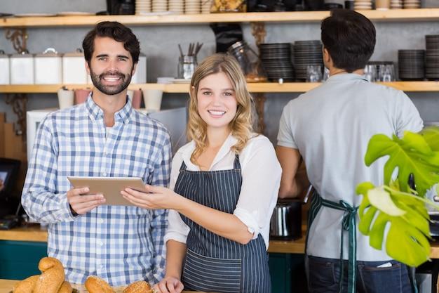 Uśmiechnięty mężczyzna i kelnerki stoi przy kontuarem używać cyfrową pastylkę