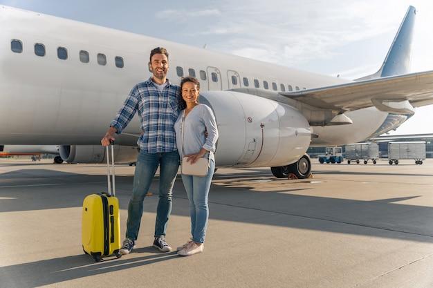 Uśmiechnięty mężczyzna i kobieta czekają razem na lot