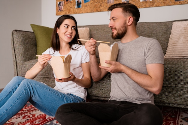 Uśmiechnięty mężczyzna i kobieta razem obiad w domu