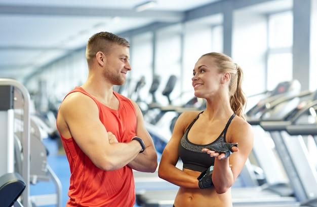Uśmiechnięty mężczyzna i kobieta rozmawia w siłowni