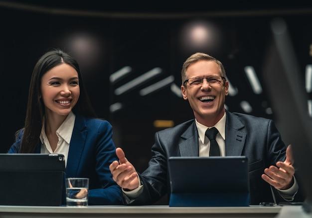 Uśmiechnięty mężczyzna i kobieta siedzący przy stole podczas konferencji biznesowej