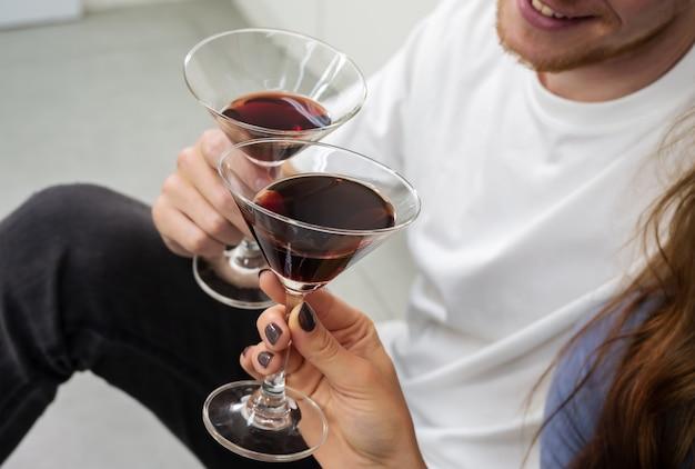 Uśmiechnięty mężczyzna i kobieta siedzi na podłodze w kuchni i brzęczące szklanki koktajli. zakochana para spędzająca razem czas, dobrze się bawiąc i pijąc w domu.