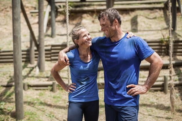 Uśmiechnięty mężczyzna i kobieta stojących z ramieniem wokół siebie w obozie dla rekrutów