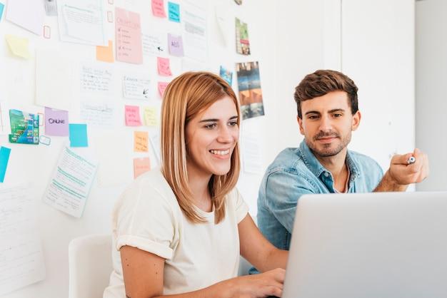Uśmiechnięty mężczyzna i kobieta surfowania w internecie