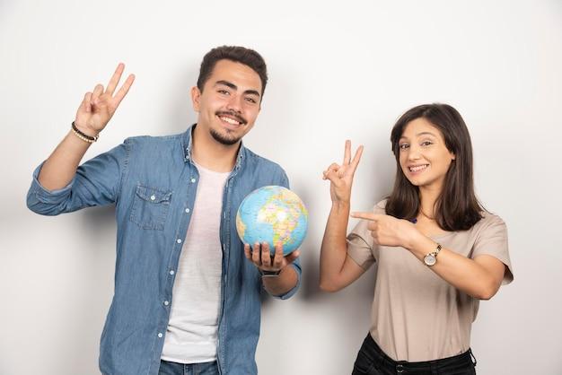 Uśmiechnięty mężczyzna i kobieta trzyma kulę ziemską i pokazując dwa palce w górę.