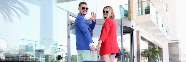Uśmiechnięty mężczyzna i kobieta w okularach przeciwsłonecznych z walizką w pobliżu budynku