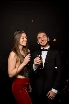 Uśmiechnięty mężczyzna i kobieta w smokingu i wieczór nosić z kieliszków napojów w pobliżu konfetti