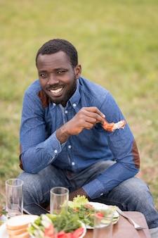 Uśmiechnięty mężczyzna jedzenie grilla na świeżym powietrzu