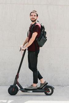 Uśmiechnięty mężczyzna jedzie hulajnoga na ulicie