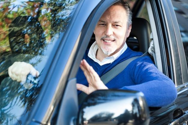 Uśmiechnięty mężczyzna jedzie jego samochód
