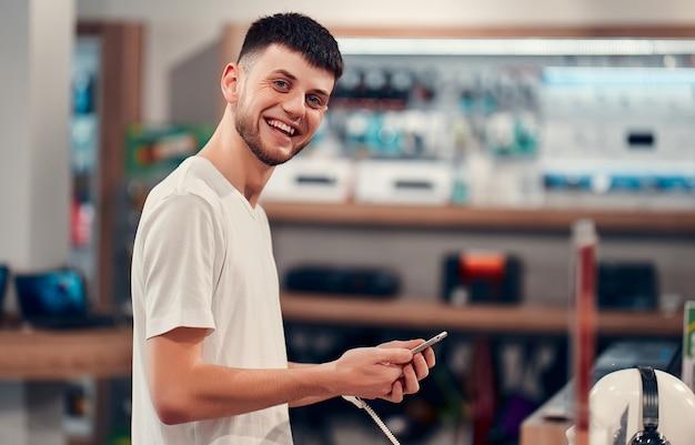 Uśmiechnięty mężczyzna kaukaski w białej koszulce wypróbowuje nowy inteligentny telefon. wnętrze sklepu technicznego.