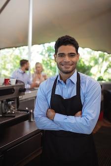 Uśmiechnięty mężczyzna kelner stojący z rękami skrzyżowanymi w restauracji