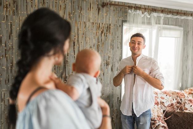 Uśmiechnięty mężczyzna kładzenie na koszula patrzeje jego żony przewożenia dziecka w domu