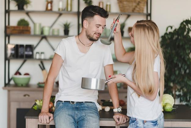 Uśmiechnięty mężczyzna kosztuje polewkę przygotowywającą kobietą w kuchni