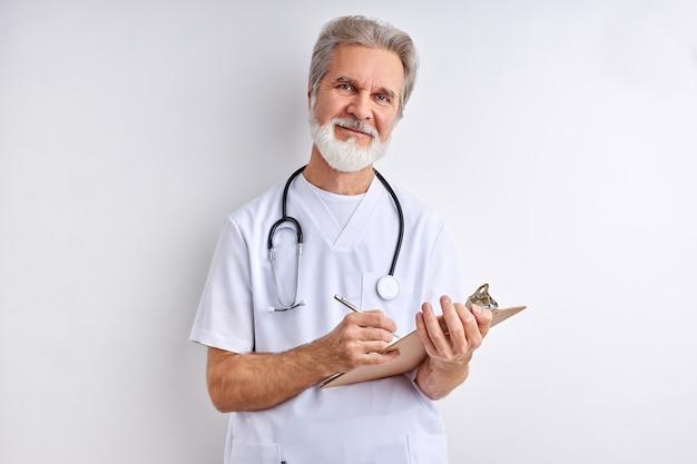 Uśmiechnięty mężczyzna lekarz robi notatki, słucha pacjenta. starszy, siwy mężczyzna udziela zaleceń lekarskich