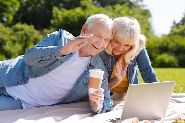 Uśmiechnięty mężczyzna leżący na kratę i trzymając kubek z kawą podczas korzystania z gadżetu do komunikacji