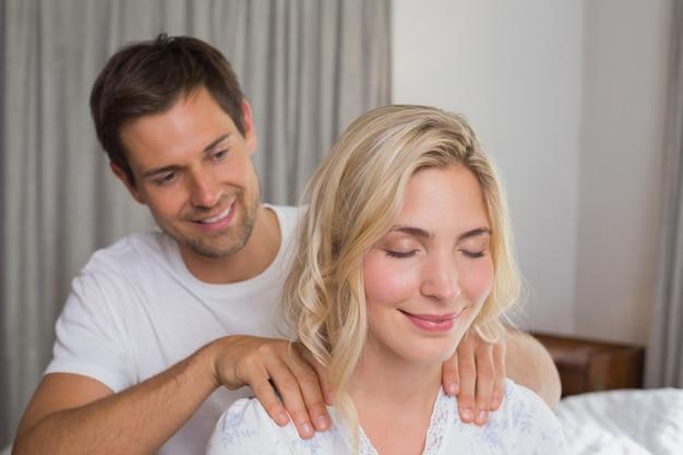 Uśmiechnięty mężczyzna masuje womans ramiona