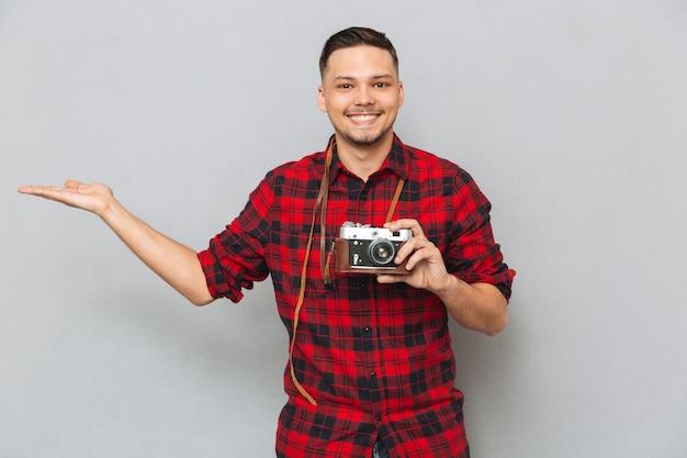 Uśmiechnięty mężczyzna mienia copyspace na funtowej i retro kamerze