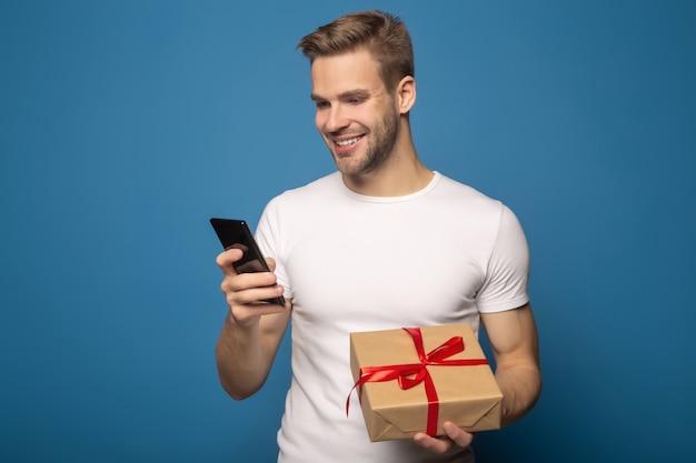 Uśmiechnięty mężczyzna mienia prezent i używać smartphone odizolowywający na błękicie