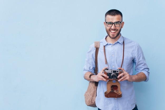Uśmiechnięty mężczyzna mruga oko podczas gdy trzymający kamery pozycję przeciw błękitnemu tłu