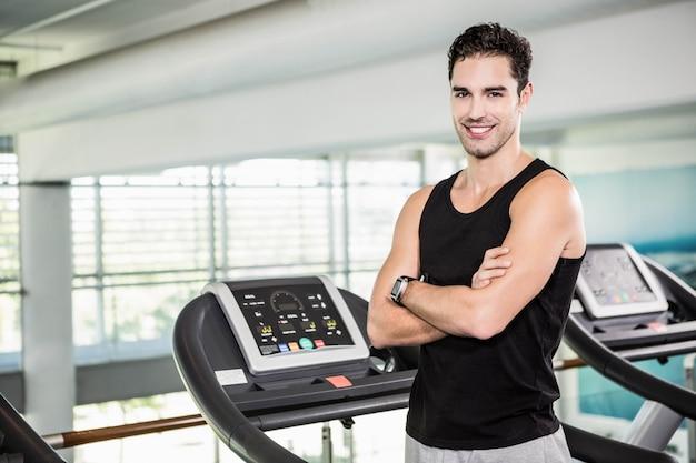 Uśmiechnięty mężczyzna na bieżni stojącej z rękami skrzyżowanymi na siłowni
