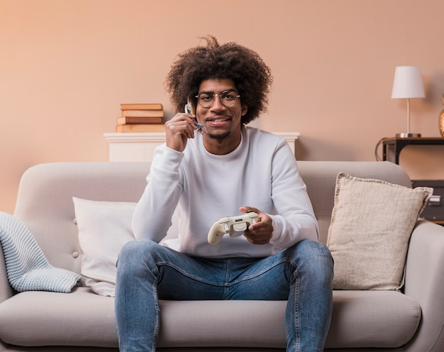 Uśmiechnięty mężczyzna na kanapie, grając w gry