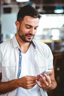 Uśmiechnięty mężczyzna na telefonie ma kawę