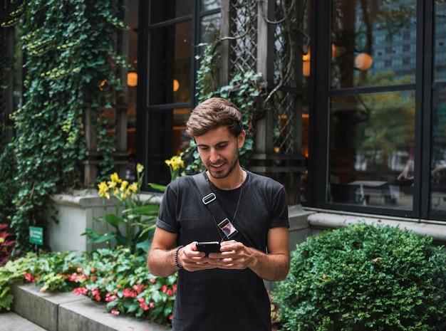 Uśmiechnięty mężczyzna na zewnątrz za pomocą smartfona