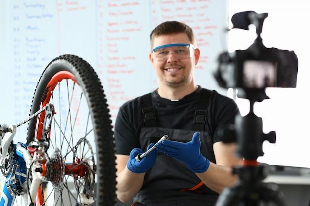 Uśmiechnięty mężczyzna naprawia rower górski za pomocą klucza