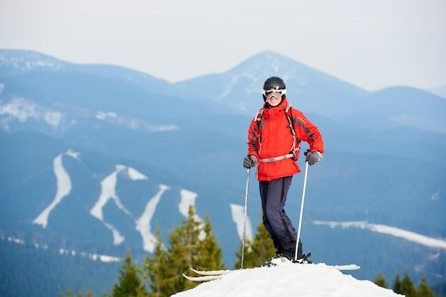 Uśmiechnięty mężczyzna narciarz stojący na szczycie wzgórza w ośrodku narciarskim bukovel