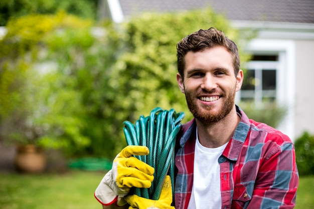 Uśmiechnięty mężczyzna niesie ogrodowego węża elastycznego w podwórku