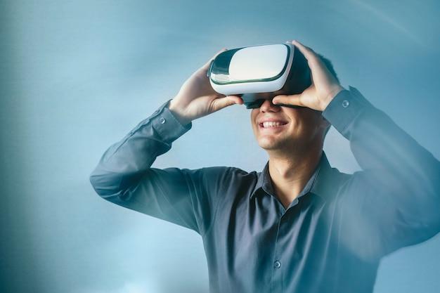 Uśmiechnięty mężczyzna nosi słuchawki wirtualnej rzeczywistości