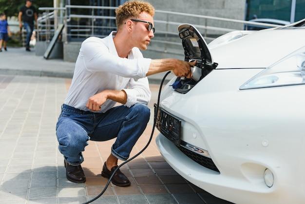 Uśmiechnięty mężczyzna odłączając ładowarkę od samochodu