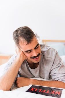 Uśmiechnięty mężczyzna ogląda netflix serie na łóżku