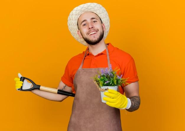 Uśmiechnięty mężczyzna ogrodnik w kapeluszu ogrodniczym i rękawiczkach trzyma kwiaty w doniczce i szpadel za plecami