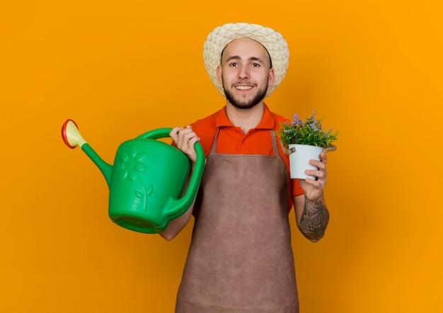 Uśmiechnięty mężczyzna ogrodnik w kapeluszu ogrodniczym trzyma konewkę i kwiaty w doniczce