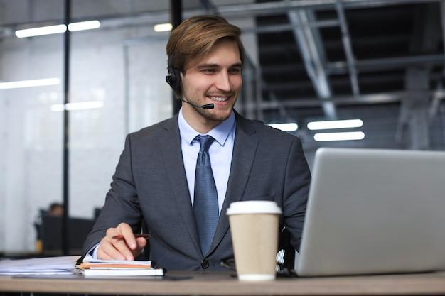 Uśmiechnięty mężczyzna operator call-center ze słuchawkami siedzący w nowoczesnym biurze, konsultujący informacje online w laptopie, wyszukujący informacje w pliku, aby pomóc klientowi.