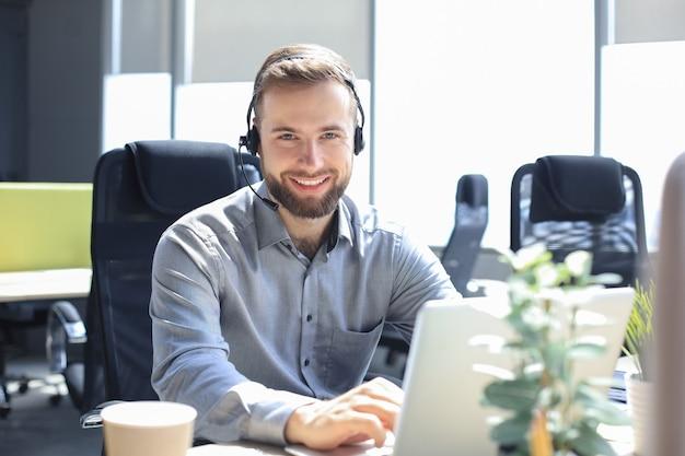Uśmiechnięty mężczyzna operator call-center ze słuchawkami siedzący w nowoczesnym biurze, konsultujący informacje online w laptopie, wyszukujący informacje w pliku, aby pomóc klientowi