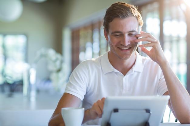 Uśmiechnięty mężczyzna opowiada na telefonie komórkowym podczas gdy używać cyfrową pastylkę