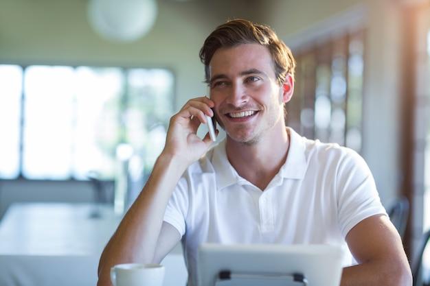 Uśmiechnięty mężczyzna opowiada na telefonie komórkowym