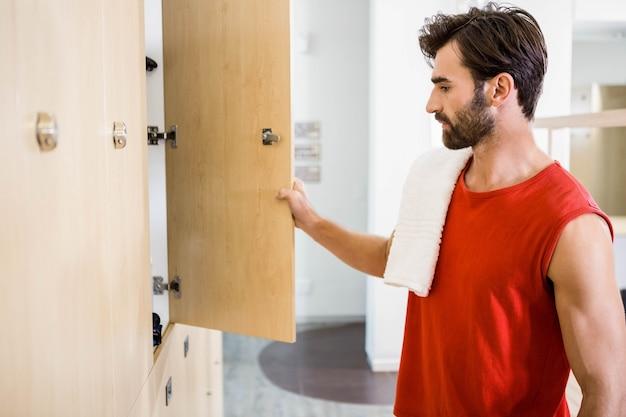 Uśmiechnięty mężczyzna otwarcia szafki w siłowni