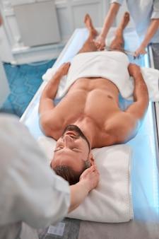 Uśmiechnięty mężczyzna pacjent przechodzi zabieg relaksującego masażu z profesjonalnymi terapeutami w klinice