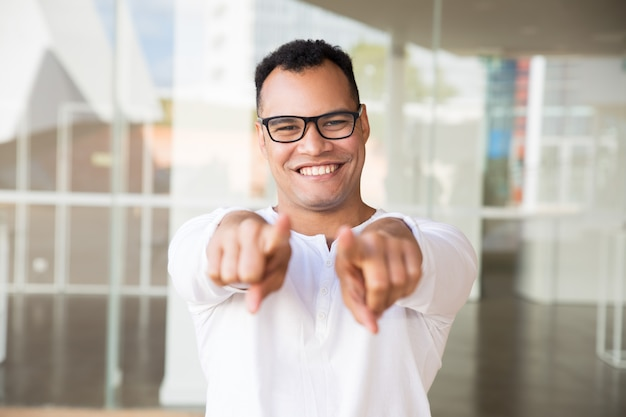 Uśmiechnięty mężczyzna patrzeje kamerę, wskazuje przy kamerą z rękami