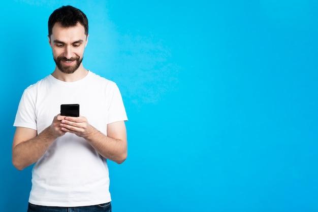 Uśmiechnięty mężczyzna patrzeje smartphone