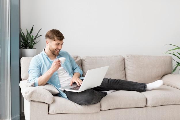 Uśmiechnięty mężczyzna pije kawę i używa laptop