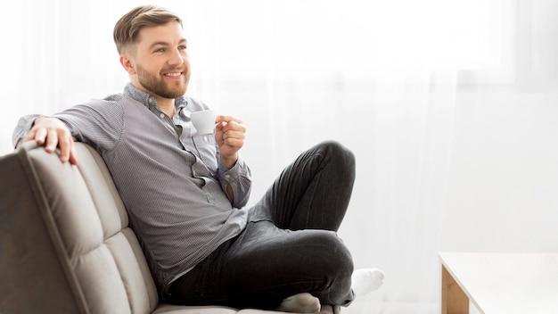Uśmiechnięty mężczyzna pije kawę na kanapie