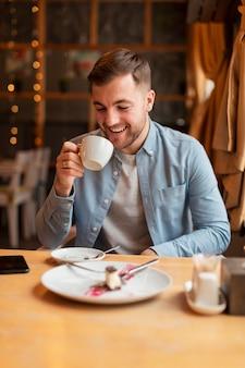 Uśmiechnięty mężczyzna pije kawę