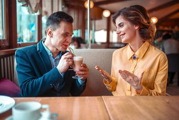 Uśmiechnięty mężczyzna pije koktajl ze słomek przeciwko szczęśliwej kobiecie w restauracji. miłość para na romantyczną randkę