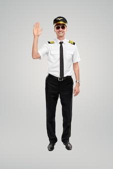 Uśmiechnięty mężczyzna pilot linii lotniczych macha ręką i uśmiecha się