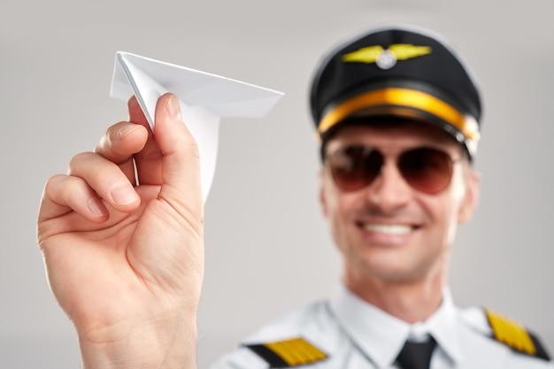 Uśmiechnięty mężczyzna pilot trzyma papierowy samolot